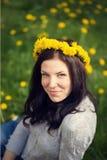 Das schöne Mädchen sitzt im gelben Löwenzahn mit einem Kranz auf Th Stockfotografie