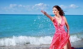 Das schöne Mädchen spritzt mit Wasser Stockfoto