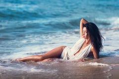 Das schöne Modell, welches das Lügen auf dem Strand aufwirft Stockfotografie