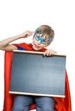 Das schöne nette Kind, das als Supermann mit lustigen Gläsern gekleidet wird, hält eine rechteckige Tafel Stockfoto