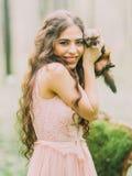 Das schöne Porträt der lächelnden Frau mit dem langen gelockten Haar im hellrosa Kleid, welches das kleine braune Frettchen umarm Stockbilder