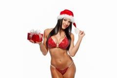 Das schöne sexy Mädchen, das Weihnachtsmann trägt, kleidet mit Weihnachten g Stockfotos