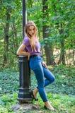 Das schöne sexy Mädchen in den Jeans und die Jacke, die unter den Bäumen im Herbst gehen, parken und werfen emotional nahe einer  Lizenzfreies Stockfoto