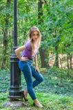 Das schöne sexy Mädchen in den Jeans und die Jacke, die unter den Bäumen im Herbst gehen, parken und werfen emotional nahe einer  Lizenzfreie Stockfotografie