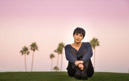 Das schöne Sitzen der jungen Frau auf Hügel bei Sonnenuntergang Stockfotos