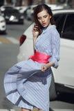 Das schöne stilvolle Brünettemädchen, das in gestreiftem weißem und blauem Kleid mit einem hellen rosa Gurt mit einem Bogen an de lizenzfreie stockbilder