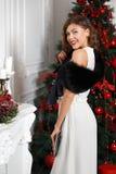 Das schöne stilvolle Mädchen, das im weißen Kleid und im schwarzen Pelzumhang auf ihm gekleidet wird, wirft nahe bei dem Baum des stockfotografie