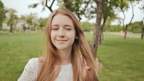 Das schöne Studentenmädchen, lächelnd, kämmt ihr langes Haar im Park Rest während der Studie stock footage