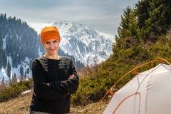 Das schöne touristische Mädchen, das nahe einem Zelt auf einem Hintergrund des Waldes steht, Schnee-bedeckte Berge mit einer Kapp Stockbilder