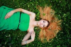 Das schöne träumende blonde Lügen auf dem Gras, oben schauend in kam Lizenzfreie Stockbilder