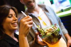 Das schönes Besuchen der jungen Frau essen Markt und das Essen des bunten Salats in der Straße stockfoto