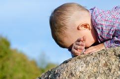 Das schüchterne Verstecken des kleinen Jungen hat Gesicht Lizenzfreie Stockfotografie
