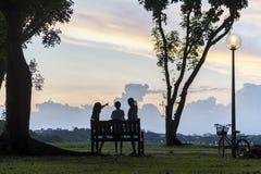 Das Schattenbild der Familie Sonnenuntergang am Park mit Fahrrad genießend parkte neben Laternenpfahl Lizenzfreies Stockfoto