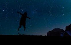 Das Schattenbild der jungen Frau springend über Sandhügel, unter den Sternen, Milchstraße und Sterne über dem Berg bei Wadi Rum v Stockfotos