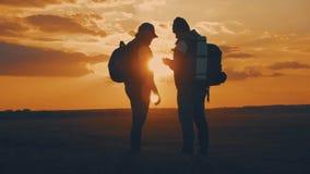 Das Schattenbild der Zwei-mannstellung auf die Oberseite des Berges mit Rucks?cken und der Gebrauch ruft f?r Navigation an Lebens stock footage