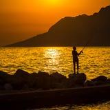 Das Schattenbild des Fischers auf dem Strand Lizenzfreie Stockfotos