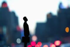 Das Schattenbild des Geschäftsmannes einen Aktenkoffer mit unscharfer Stadt halten beleuchtet hinter ihm Stockfoto