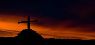 Das Schattenbild des hölzernen Kreuzes auf brennendem Himmelhintergrund Stockbilder