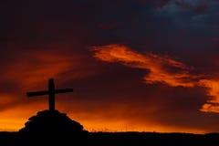 Das Schattenbild des hölzernen Kreuzes auf brennendem Himmelhintergrund stockfoto