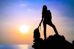 Das Schattenbild des Mädchens mit Rucksack bei Sonnenuntergang Lizenzfreies Stockbild