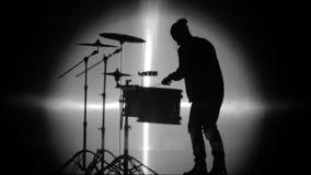Das Schattenbild des Schlagzeugers im Lichtfleck stock video