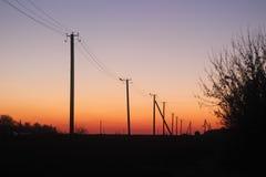 Das Schattenbild des Strompfostens in der Dämmerung Stockbild