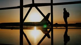 Das Schattenbild des touristischen Kerls, der den Start des Flugzeugs aufpasst und ein enormes Flugzeug steht am Flughafen führt stock video