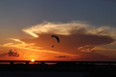 Das Schattenbild eines angetriebenen Gleitschirms, paramotor, vor einem großartigen orange Abendhimmel in Süd-Texas, USA Stockfotos