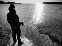 Das Schattenbild eines Fischers, der das Spinnen an der Dämmerung wirft Der aktive Mann fischt auf Meer Stockbild