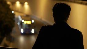 Das Schattenbild eines Mädchens steht über einem Tunnel mit einer Maschine, die durch läuft stock video