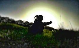 das Schattenbild von einem Rastafarian, das auf dem Gras im Sonnenuntergang sitzt Lizenzfreies Stockbild