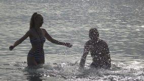 Das Schattenbild von jungen Leuten des Mannes und der Frau, die im Meer stehen und Wasserhände spritzen, Zeitlupe stock video