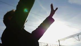 Das Schattenbildgeschäftsmannanheben überreicht unscharfe Stadt auf Sonnenunterganghintergrund stock video footage