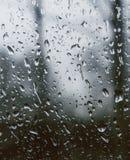 Das Schauen aus einem Fenster heraus, das mit Regen bedeckt wird, fällt stockfoto