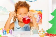Das Schauen des Mädchens malt Ball des neuen Jahres für Weihnachtsbaum Stockfoto
