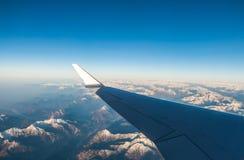 Das Schauen durch die Fensterflugzeuge während des Fluges ein Schnee bedeckte Italiener und Osterreich Stockbilder
