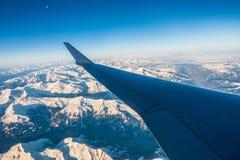 Das Schauen durch die Fensterflugzeuge während des Fluges ein Schnee bedeckte Italiener und Osterreich Lizenzfreies Stockbild