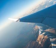 Das Schauen durch die Fensterflugzeuge während des Fluges ein Schnee bedeckte Italiener und Osterreich Lizenzfreies Stockfoto