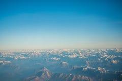 Das Schauen durch die Fensterflugzeuge während des Fluges ein Schnee bedeckte Italiener und Osterreich Lizenzfreie Stockfotografie