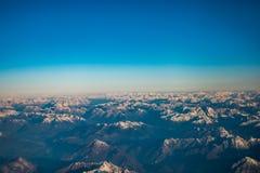 Das Schauen durch die Fensterflugzeuge während des Fluges ein Schnee bedeckte Italiener und Osterreich Stockfotos