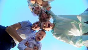 Das Schießen wird von unten nach oben, gegen den blauen Himmel geleitet, die junge Familie des Ganzen umfasst und in einem Kreis  stock video footage