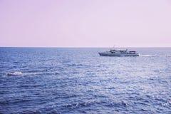 Das Schiff segelt auf das Meer während eines rosa Sonnenuntergangs Lizenzfreies Stockbild