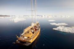 Das Schiff segelt unter den Eisbergen in der Antarktis stockbild