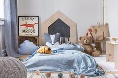 Das Schlafzimmer des blauen Jungen mit Spielwaren und Holzmöbel, wirkliches Foto mit Modell stockbilder