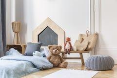 Das Schlafzimmer des stilvolles Kindes im Wohnungshaus Grauer Puff auf dem Parkett, Holztisch mit Taschen und Spielwaren, Bett mi stockbilder