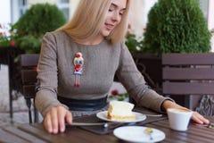 Das schöne blonde Mädchen, das am Café mit Tasse Kaffee- und Kuchenarbeiten sitzt und zeichnet Skizzen in einem Notizbuch Stockbilder