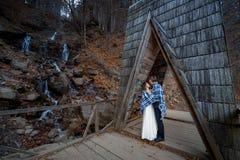 Das schöne Hochzeitspaar, das in der Decke eingewickelt wird, umarmt auf der Holzbrücke Flitterwochen an den Bergen Lizenzfreies Stockfoto
