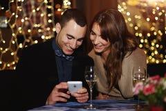Das schöne junge Paar, das in einem Restaurant und im Kerl sitzt, deckt seine Lieblingsfotos auf Lizenzfreie Stockfotografie