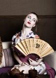 Das schöne Mädchen, das als Geisha gekleidet wird, hält sie einen chinesischen Fan Geishamake-up und -haar kleideten in einem Kim Lizenzfreies Stockbild