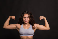 Das schöne Mädchen, das Sport durchführt, trainiert auf einem dunklen Hintergrund Lizenzfreie Stockfotos